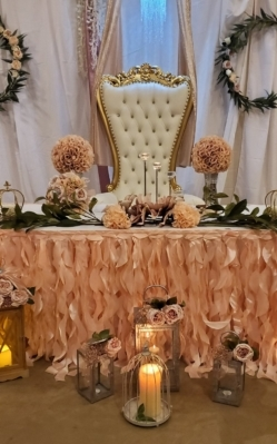 Photo of event decoration for wedding. Large throne chair, light pink table cloth, greenery. 249 by 399 pixels